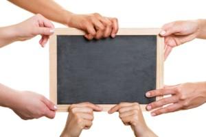 Viele verschiedene Hände halten eine leere schwarze Tafel